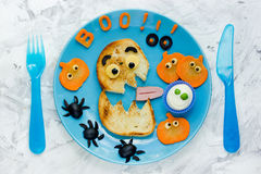 Halloween party ideas for kids - monster toast with pumpkin, oli. Ve spiders and white ghost sauce. Fun with food composition on the blue plate top view Stock Photos