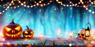 Halloween Party - Jack O` Lanterns And String Lights On Table. In Misty Forest royalty free stock photo