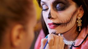 Halloween party, make-up artist draws a terrible makeup on the face of a brunette woman for a Halloween party. in the