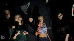 Halloween party, night, twilight, in the rays of light, young people frighten the spectators, everyone is dressed in