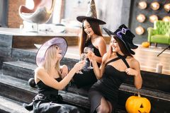 Three girls sit and clink glasses with champagne stock photos