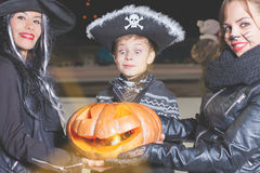 Halloween party! Young women and boy holding pumpkin. Halloween party! Horror and magic holiday night. Young women like witch and cat role, pirate boy holding Royalty Free Stock Photography