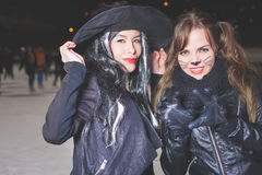 Halloween party! Young women like witch and cat role. Cat and witch carnival mask. Role-playing games. Fashion girls Royalty Free Stock Images