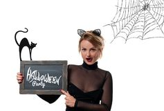 Halloween Partyt. Woman with carnival cat ears. Beautiful woman with carnival cat ears holding chalkboard with text Halloween Party Stock Photo