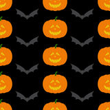 Halloween pattern with pumpkin and bat. Seamless pattern with repeating frightful orange Halloween pumpkin with evil face and grey flying bat  on dark black Royalty Free Stock Photo