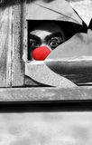 Halloween Peek A Boo. Peeking Through A Broken Window Pane A Creepy Ghoulish Clown Watches The Halloween Peek A Boo Royalty Free Stock Photos