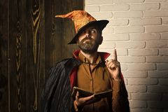 Halloween philosophy, wisdom and knowledge concept. Mystic manuscript and fairytale. Man in witch hat, cloak with raised finger. Magic and evil spell. Wizard stock photo
