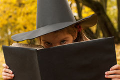 A Halloween photo of a little girl representing a wicked witch and looking over from a magic book Stock Photo