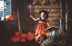 Halloween piccola strega del bambino con la bacchetta magica e la lettura del MAG Immagine Stock