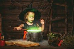 Halloween piccolo bambino della strega che cucina pozione in calderone con immagini stock libere da diritti