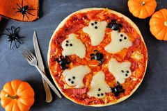 Halloween pizza, above scene with decor on black background. Halloween pizza with ghosts and spiders, above scene with decor on a black background Royalty Free Stock Photos