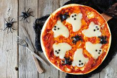 Halloween pizza above scene with decor on rustic wood. Halloween pizza above scene with decor on a rustic wood background Royalty Free Stock Photo