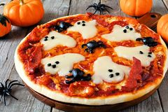 Halloween pizza close up on rustic wood. Halloween pizza with ghosts and spiders, close up on a rustic wood background Royalty Free Stock Image