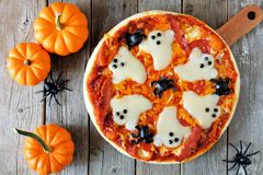Halloween pizza, above scene with decor on wood. Halloween pizza with ghosts and spiders, above scene with decor on a rustic wood background Royalty Free Stock Images