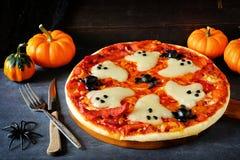 Halloween pizza, close up on a dark background. Halloween pizza with ghosts and spiders, close up on a dark background Royalty Free Stock Photos