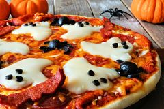 Halloween pizza with ghosts and spiders, close up. On a rustic wood background Royalty Free Stock Photo