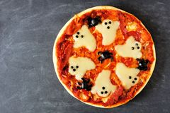 Halloween pizza overhead view on slate. Halloween pizza with ghosts and spiders, overhead view on a slate background Royalty Free Stock Image