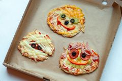 Halloween pizza with monsters, above scene with decor on a craft paper box background, idea for home party food. Halloween pizza with monsters, above scene with royalty free stock photos