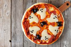 Halloween pizza overhead view on rustic wood. Halloween pizza overhead view on a rustic wooden background Royalty Free Stock Photography