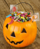 Halloween plastic pumpkin filled with candy on wooden table - 1 Royalty Free Stock Photography