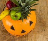 Halloween-Plastikkürbis voll von Früchten Lizenzfreies Stockbild