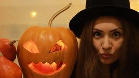 Halloween Pompoen De vrouw in de zwarte hoed het drukt emoties met grote ogen uit - verras, vrees, angst r stock videobeelden