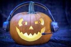 Halloween-pompoen in hoofdtelefoons - prentbriefkaar Stock Foto's