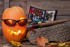 Halloween-pompoen met het waden van laarzen en vlieg-vist Stock Fotografie