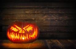 Halloween-pompoen op donkere, houten achtergrond Stock Afbeeldingen