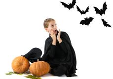 Halloween portrait of the surprised and frightened girl in the witch costume stock image