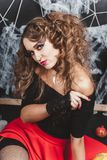 Halloween portrait of witch girl sitting on the floor with black wall and spider web on background. Wears a blouse and Royalty Free Stock Image