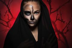 Halloween portrait of young beautiful girl in a black hood. skeleton makeup half face. stock photo