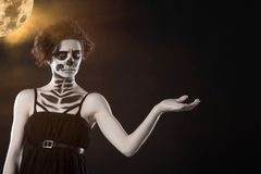 Halloween. Portrait of young beautiful girl with make-up skeleton on her face. Against the black sky and moon. Copy space stock photography