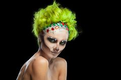 Halloween. Portrait of young beautiful girl with make-up skeleton on her face. And green hair. Isolated on black royalty free stock photos