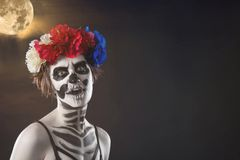 Halloween. Portrait of young beautiful girl with make-up skeleton on her face. Against the black sky and moon. Copy space royalty free stock image