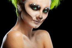 Halloween. Portrait of young beautiful girl with make-up skeleton on her face. And green hair. Isolated on black stock images