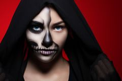 Halloween. Portrait of a young beautiful girl with skeleton makeup on her face. Girl in black hood on a bright red background Stock Image