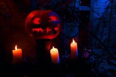Halloween - potiron, bougies et une horloge sur des feuilles et des rondins avec Photographie stock