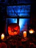 Halloween - potirons, bougies et une lampe sur des feuilles et des rondins avec Image stock