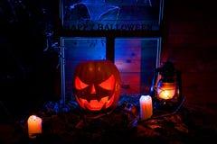 Halloween - potirons, bougies et une lampe sur des feuilles et des rondins avec Images stock