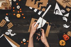 Halloween preparation. Hands making halloween cards and decoration using craft paper Stock Photo