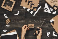 Halloween preparation. Hands making halloween cards and decoration using craft paper Royalty Free Stock Photo