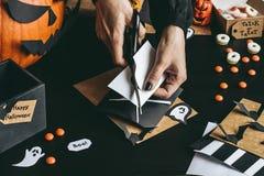 Halloween preparation. Hands making halloween decoration using craft paper Stock Photo