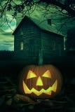Halloween pumpa framme av ett spöklikt hus Royaltyfria Bilder