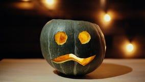 Halloween-pumpa med läskigt lysande ansikte mot ljus bakgrund stock video