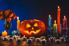 Halloween Pumpkin with alot of candles and flowers in dark lighting. Trick or treat concept on blue and red background. Halloween Pumpkin with candles and Royalty Free Stock Photo