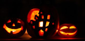 Banner Halloween pumpkin background, three pumpkins with dark black background. Two scary faced pumpkins and house