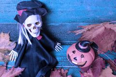 Halloween pumpkin and blurred skeleton witch over autumn leaves on wooden background, toned in blue. Halloween concept royalty free stock photo