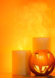 Halloween pumpkin border. Halloween pumpkin holiday border, with candles and smoke, traditional jack-o-lantern over warm yellow light, night party decoration Royalty Free Stock Photo