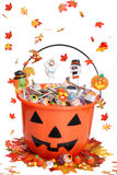 Halloween pumpkin bucket with candy fall leaves Royalty Free Stock Photos